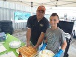 TJ and his helper serving BBQ sliders