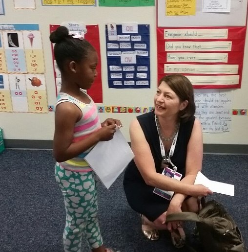 Kim Jacobson, education grant director of the Full Circle Fund in the San Francisco Bay area talks with Olive Elementary first-grader Naomi Vasquez.