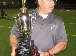 Vista City Councilman John Aguilera presents the championship trophy.